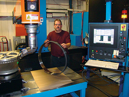 "Scott Stang, Manufacturing Technology Manager for Hi-Tek is pictured with an aerospace engine component processed on the company's newly acquired Laserdyne 795XL Beam Director with fiber laser. The system pictured is equipped with a rotary table which allows drilling ""on-the-fly"" cooling holes at compound angles at high speed and with high precision."