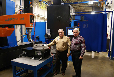 Cletis Jackson, president (left) and Gary Griessmann, vice president and engineering manager are the founders in 1980 of the successful and rapidly growing Hi-Tek Manufacturing Company. They are showing an aerospace turbine component ready for processing on their recently acquired Laserdyne 795XLBeamDirector with a fiber laser. This laser system produces trepan and percussion drilled cooling holes in large and complex aerospace components made of high temperature super alloys.